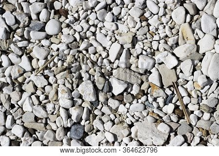 Small Pebbles With Rounded Stones Close-up For Background. Stone Surface On The Bank Of The River Se