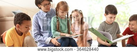 Young Nanny Reading Book And Little Children Indoors. Banner Design