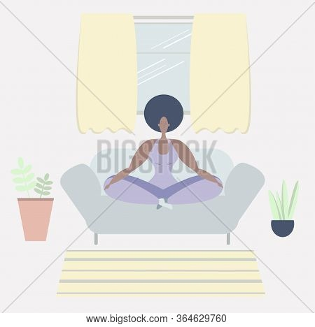 A Black Woman Meditates. A Black Woman Meditates In The Lotus Position On A Sofa. Yoga Classes At Ho