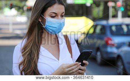 Covid-19 Pandemic Coronavirus Mobile Application - Young Woman Wearing Surgical Mask Using Smart Pho