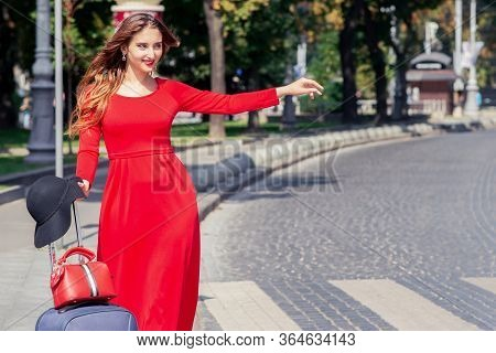 Smiling Young Woman With Suitcase Is Catching Taxi On The City Street. Catching A Taxi.