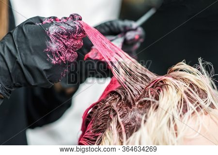 Closeup Of The Hands Of A Hairdresser In Black Gloves Dye The Hair Strand Of The Clients Girl Red. H