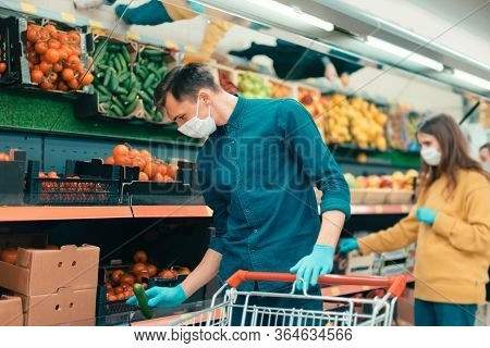 Shoppers In Protective Masks Choosing Fruit In The Supermarket