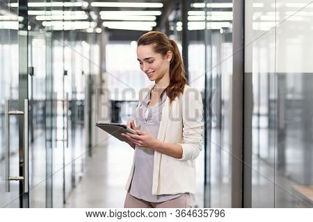 Successful Young Business Lady In Glasses Revisions Company Information On Tablet Pc While Going Alo