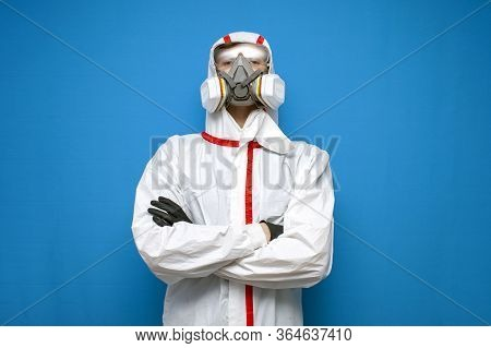 Disinfector Man In A Protective Suit And A Respirator On A Blue Isolated Background, Disinfection Se