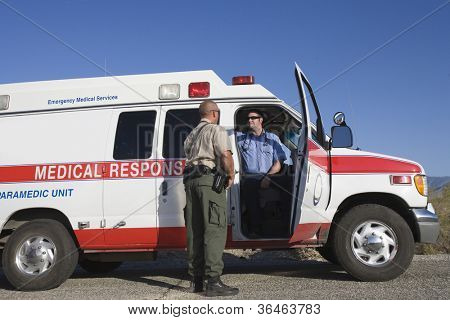 Full length of a traffic cop talking with EMT doctor in ambulance