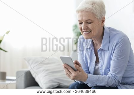 Home Leisure For Seniors. Happy Elderly Woman Using Smartphone At Home, Texting To Friends Or Browsi