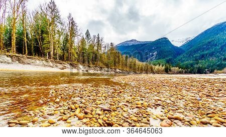 Iron Oxide Stained Rocks Lining The Shore At Low Water In The Squamish River In The Upper Squamish V