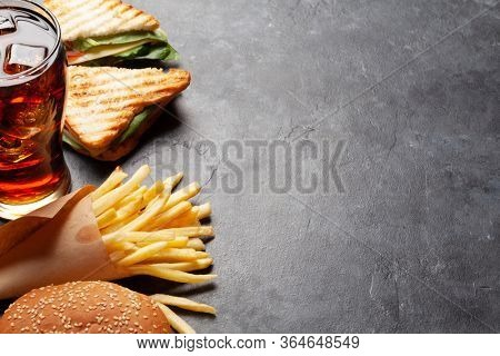 Club sandwich, potato fries chips and glass of cola drink with ice. Fast food take away. With copy space