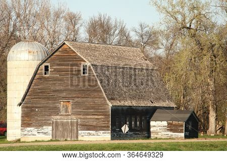 A Old Barn On A Farmstead In Rural Eastern North Dakota With Attached Milk House And A Silo.