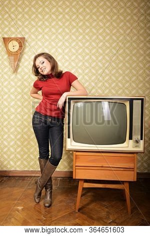 Young smiling ecstatic woman looking at camera in room with vintage wallpaper and retro TV set, retro stylization 60-70s.
