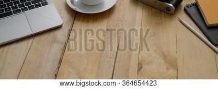 Cropped Shot Of Modern Rustic Worktable With Laptop, Supplies, Coffee Cup And Copy Space