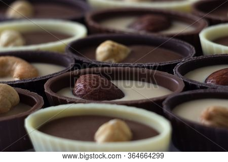 Chocolate Candies With Filling And Nuts, Sweets Background. Oval Sweets Made Of Black, Milk And Whit