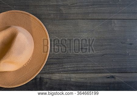 brown hat on dark wooden background with place for text. elegant accessories. Minimalistic concept o