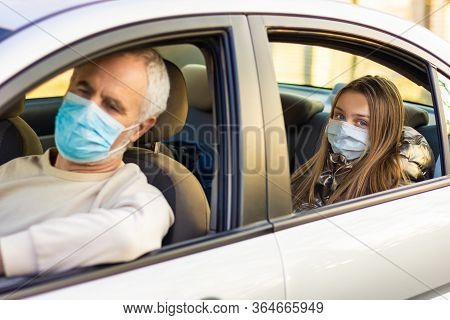 Senior Man In A Medical Face Mask Driving A Car. Coronavirus Pandemic Concept. Road Trip, Travel And