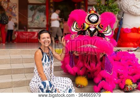 A European Tourist Girl At A Chinese New Year Celebration In A Chinese Temple Is Photographed With A