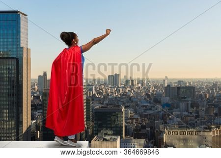 women's power and people concept - happy african american woman in red superhero cape over tokyo city skyscrapers on background