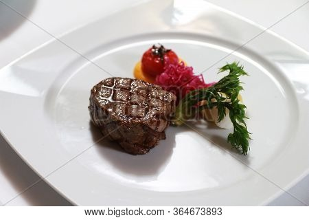 Serving A Steak On A White Plate With Tomato, Vegetables Garnish. Fancy Dinner Main Course, Steak Wi