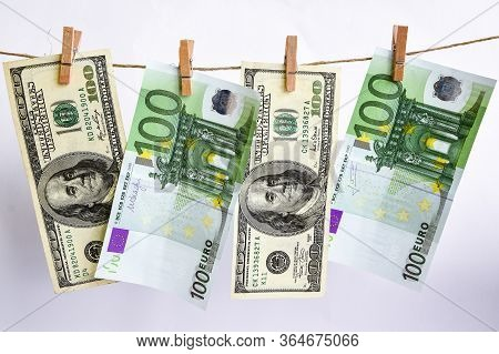 100 Dollars And Euros On A Rope, Dollars With A Clothespin On A Rope Isolated On A White Background,