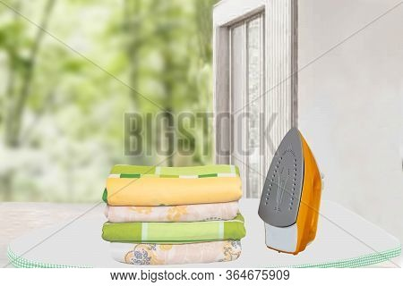 Household Laundry Ironing. Close-up Of A Yellow Electrical Iron And A Stack Of Ironed Clothes On An