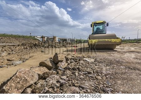 A Steamroller Paving The Ground To Build A Road