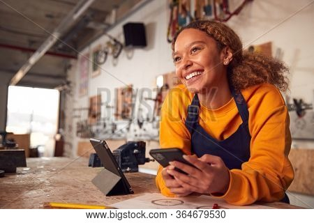 Female Business Owner In Workshop Using Digital Tablet And Holding Mobile Phone