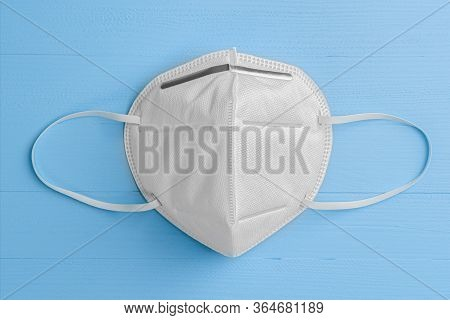 N95 Respiratory Mask On A Blue Wooden Background With Elastic Bands For The Ears. White. Copyspace.