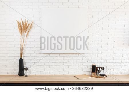 Large White Brick Wall And Canvas Fragment In The Center With Place For Text. Wooden Table With Blac
