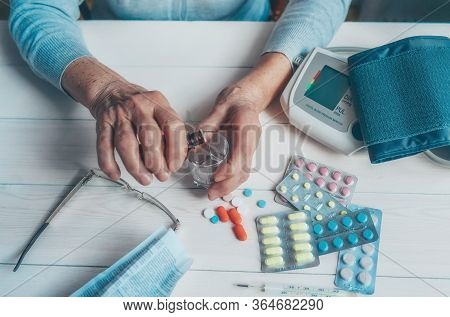 Senior Wrinkled Hands With Blood Pressure Measure Cuff, Medicine Bottle, Glass, Colorful Pills, Ther