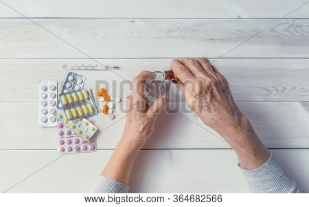 Senior Hands With Medicine Bottle Putting Drops In A Glass, Pills, Tonometer, Thermometer On A Table