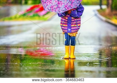 Happy Child Girl With An Umbrella And Rubber Boots  Jumping In Puddle At The Spring Day Walk.