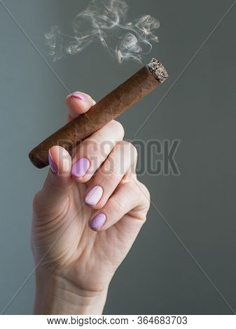 Cuban Cigar In Hand. A Woman Hand Holding A Burning Cigar.