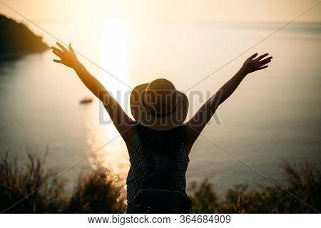 Young Asian Woman Traveler With Backpack And Hat Lifting Up Two Hand With Happiness While Looking Su