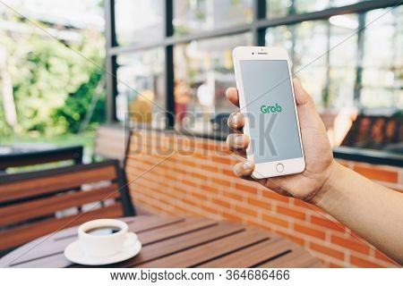 Chiang Mai, Thailand - Feb.15,2020: Man Holding Apple Iphone 8 Plus With  Grab Apps On Screen. Grab