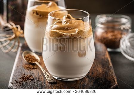 Korean Trendy Drink Dalgona Coffee From Instant Coffee, Milk And Ice On Old Wooden Board. Modern Dri