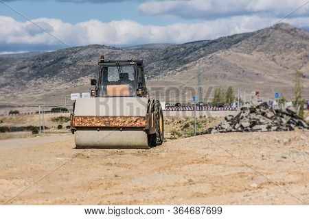 Steamroller In The Process Of Building A Road, Moving And Drilling Ground And Rock