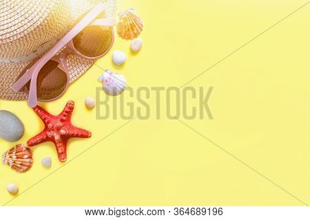 Top View Of Sun Glasses, Hat And Shells With A Starfish Sea Pebbles. Summer Vacation Background. Sum