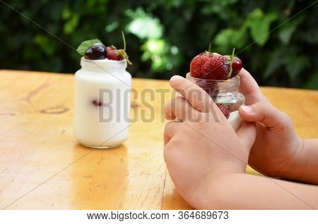 Cute Little Boys Hold In Their Hand A Jar Of Yogurt Or Pudding With Their Strawberries And Cherries,