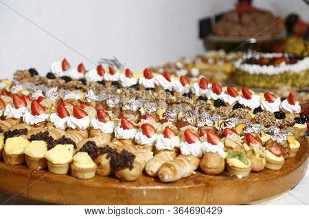 Buffet With Sweets. Fruits And Other Sweets On Dessert Table. Rows Of Tasty Looking Desserts In Beau
