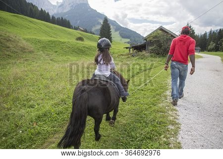 Horse Ride In The Mountains. Horse Riding. Little Girl Is Riding A Horse, Dolomites Mountain In The