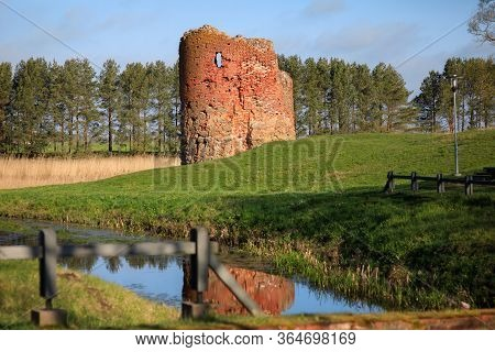 Old Collapsed Tower Of A Water Mill On The River Bank On A Clear Sunny Day, Piltene, Latvia