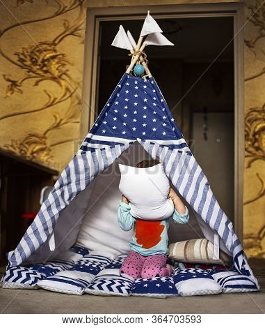 Little Girl Play In A Teepee In Her Children's Room. Entertainment For Kids At Home. Lesson For Chil