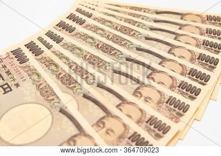 Close-up Of 100,000 Yen Stacked In Layers Of 10,000 Yen Banknotes. Isolated On White Background. Hor