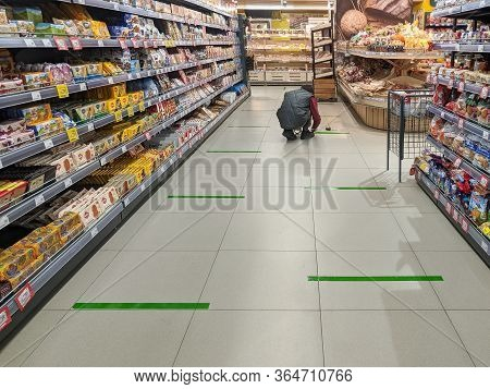 Tver, Russia - 04 29 2020: A Supermarket Employee Tapes Social Distancing Lines Across A Supermarket