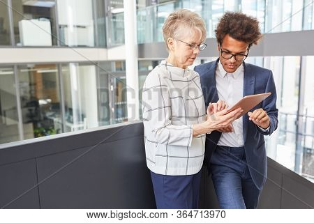 Senior and trainee research together on the Internet using tablet computers
