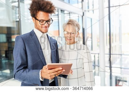 Young trainee and older businesswoman are happy about new website or news