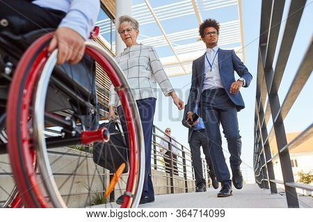 Business people and wheelchair users on a ramp in front of the office for inclusion