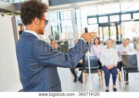 Blind business man as a speaker or life coach at a conference or congress