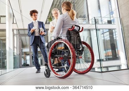 Inclusion and diversity in the business office with a woman in a wheelchair in the company