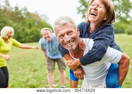 Vital seniors play together in the park in the summer and ride piggyback